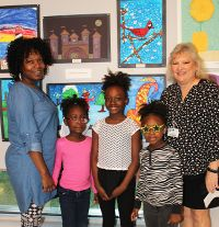 students and family standing in front of drawings